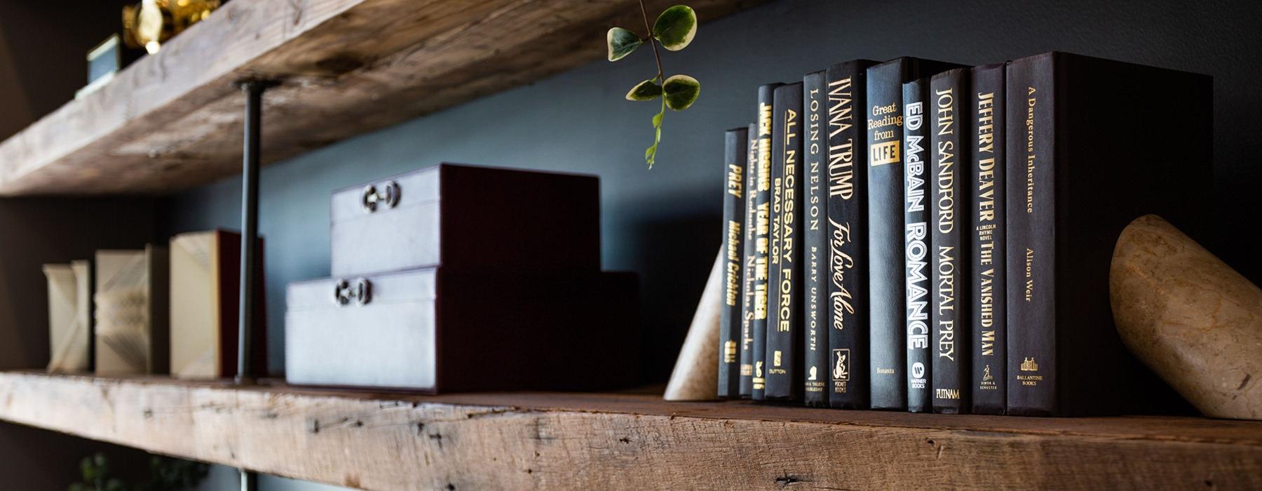 staged wood bookshelves against dark, bluish grey wall